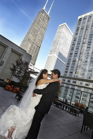 bride-and-groom-hug-on-rooftop-with-pumpkins-and-skyscrapers