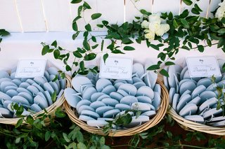 beachside-wedding-with-light-blue-flip-flops-in-wicker-baskets-surrounded-by-greenery-white-roses