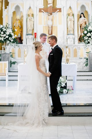 wedding-ceremony-bride-in-berta-wedding-dress-groom-at-altar-with-officiant-church-in-denver-parish