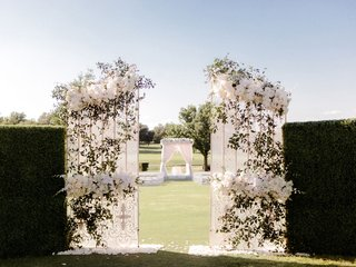 outdoor-ceremony-on-golf-course-hedge-boxwood-wall-with-white-gate-greenery-white-flowers