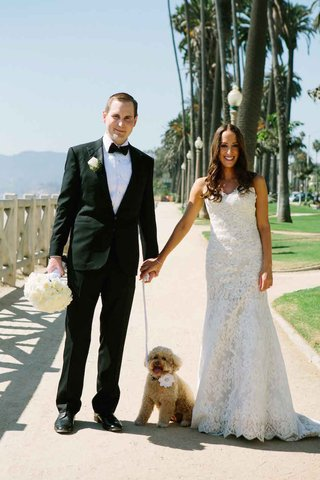 groom-in-a-black-tuxedo-bride-in-an-alencon-lace-dress-with-dog-wearing-a-white-flower-on-collar