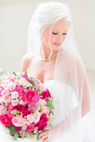 bride-in-strapless-wedding-dress-updo-veil-pink-rose-bouquet-large-wedding-portrait