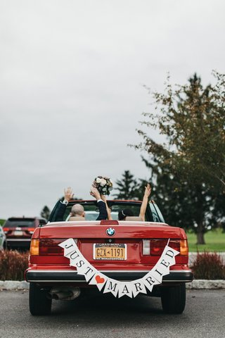 bride-and-groom-with-arms-raised-in-vintage-red-bmw-convertible-with-just-married-banner