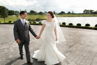 bride-in-an-off-the-shoulder-fit-and-flare-sottero-and-midgley-lace-dress-groom-in-grey-suit-pond