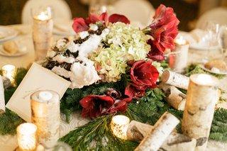winter-wedding-centerpiece-of-evergreen-red-amaryllis-green-hydrangeas-fake-snow-on-pinecones