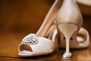 badgley-mischka-wedding-shoes-with-bedazzled-accent-displayed-with-rings