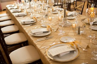 tan-table-linens-with-gold-rimmed-chargers-and-glassware