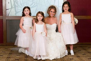 bride-kneeling-down-with-three-flower-girls
