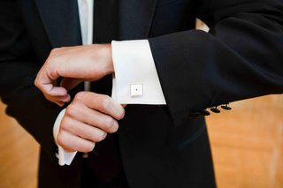groom-wearing-ivory-cuff-links-with-diamond-border