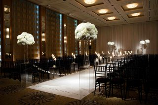 ghost-pedestals-and-black-chairs-along-aisle
