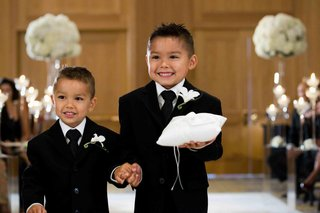 little-boys-in-tuxedos-holding-white-ring-pillow