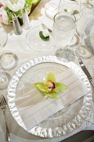 silver-rimmed-charger-plate-white-napkin-and-green-orchid