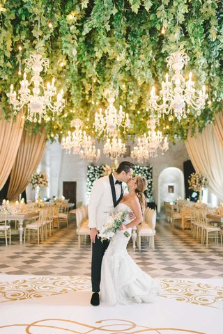 wedding-portrait-with-reception-decor-bride-groom-kiss-on-white-gold-dance-floor-checkerboard
