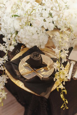 black-napkin-rose-polka-dotted-plate-gold-flatware