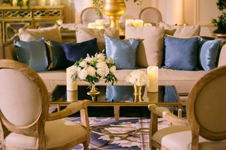 wedding-reception-lounge-gold-mirror-coffee-table-white-flowers-candles-light-blue-and-navy-pillows