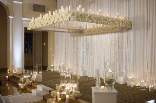 clear-ceremony-structure-with-white-flowers-and-candles-white-aisle-runner-candles-on-floor