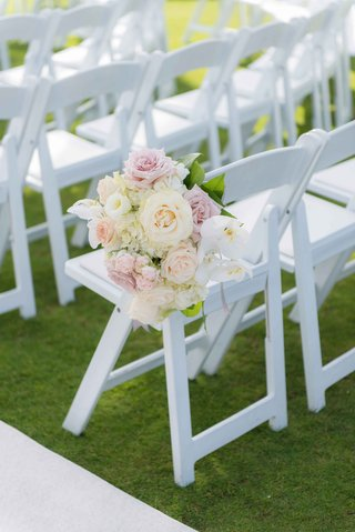 white-ceremony-chair-on-grass-lawn-with-white-and-pink-rose-orchid-hydrangea-flower-arrangement