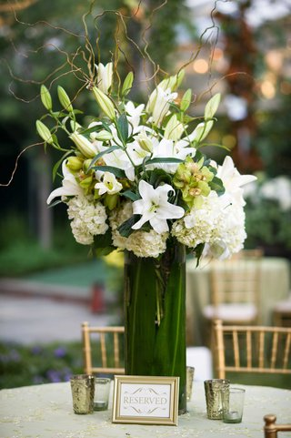 white-linen-with-gold-details-and-tall-flower-arrangement-of-white-lily-hydrangea-and-green-orchid