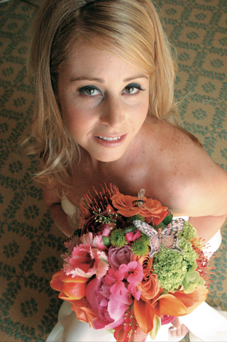 bride-holds-bouquet-of-pink-orange-and-green