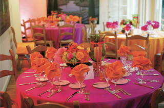 pink-tablecloth-with-orange-napkins-and-bright-flowers