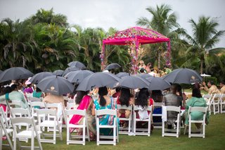 guests-holding-black-umbrellas-during-outdoor-wedding-ceremony-in-the-rain