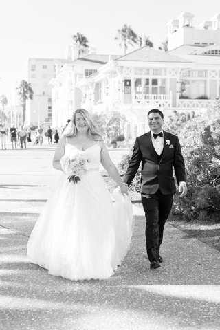 black-and-white-photo-of-a-bride-and-groom-holding-hands-wedding-portrait-santa-monica-casa-del-mar