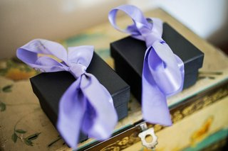 two-small-black-boxes-are-tied-with-light-purple-ribbon-bows-for-wedding-guests-on-jewelry-box