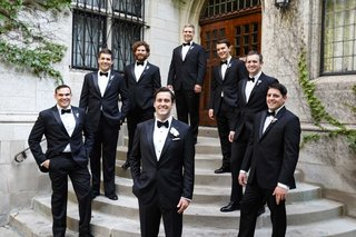 groom-and-groomsmen-in-tuxedo-suits-with-black-bow-ties-white-pocket-squares-boutonniere