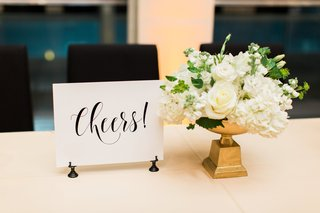 cheers-sign-next-to-small-white-floral-arrangement-on-gold-base
