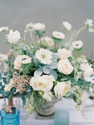 low-floral-arrangement-of-white-and-blush-flowers-with-green-foliage-on-blue-white-tablescape