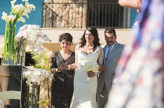 bride-and-parents-walk-down-aisle-lined-with-white-calla-lilies-and-orchids