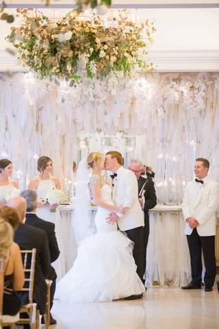 bride-in-hayley-paige-mermaid-gown-kissing-groom-in-white-tuxedo-jacket-white-ribbon-ceremony-decor