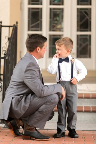 groom-in-grey-suit-and-black-shoes-talks-to-to-ring-bearer-in-grey-pants-navy-suspenders-bow-tie