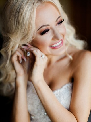 bride-in-smokey-eye-makeup-with-pink-lipstick-blonde-hair-putting-on-diamond-earring-before-wedding