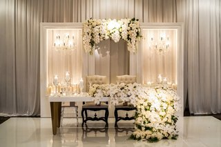 lacquer-sweetheart-table-with-two-chandeliers-on-both-sides-candles-tall-candleholders-orchid