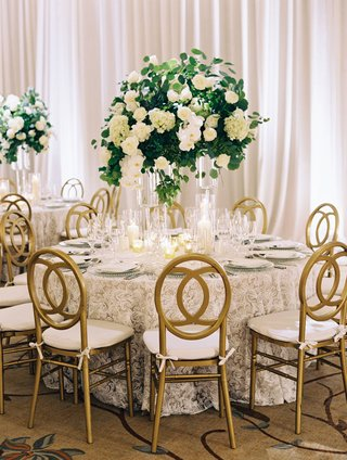 wedding-reception-ballroom-gold-chairs-lace-table-linen-tall-centerpiece-greenery-white-orchids