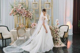 an-a-line-jinza-bridal-gown-featuring-strapless-neckline-and-long-veil-pink-floral-arrangements