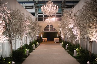 wedding-reception-entrance-to-dinner-space-cherry-blossom-trees-and-greenery-chandeliers-drapery