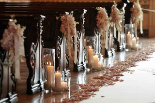 pillar-candles-and-flowers-next-to-wooden-pews
