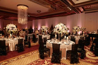ballroom-tables-surrounded-by-black-chair-covers