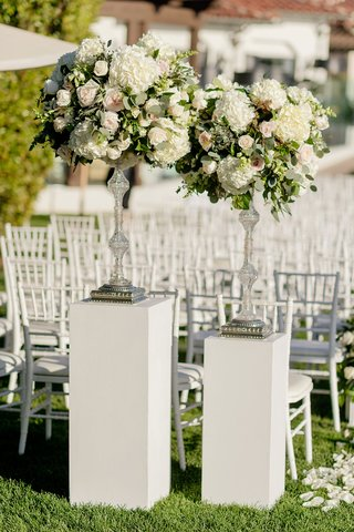 crystal-riser-with-greenery-white-hydrangea-rose-in-white-pink-white-riser-white-chairs-ceremony