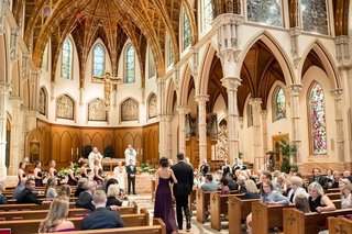 bridesmaid-and-groomsman-processional-church-wedding-chicago-tall-arches-stained-glass-greenery