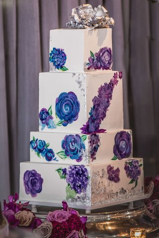 wedding-cake-with-white-square-tiers-painted-with-blue-and-purple-flowers