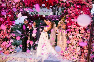 wedding-ceremony-kiss-with-pink-confetti-pink-flowers-chuppah-first-kiss