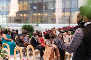 musician-at-front-of-ceremony-playing-songs-on-electric-violin-wedding-entertainment-idea