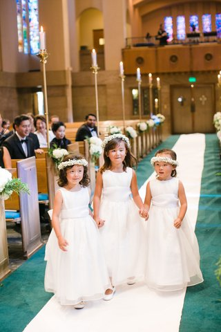 three-flower-girls-in-white-dresses-white-flower-crowns-holding-hands-down-aisle-white-runner