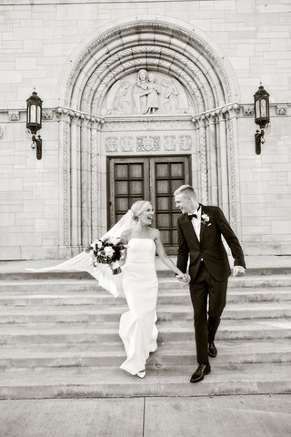 black-and-white-photo-of-bride-and-groom-running-down-church-steps-as-husband-and-wife