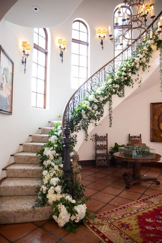 wedding-reception-at-bride-family-home-staircase-with-iron-railing-greenery-white-flowers