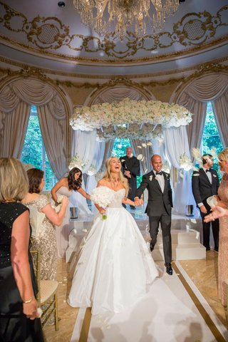bride-in-strapless-reem-acra-wedding-dress-and-groom-holding-hands-walking-on-white-gold-aisle