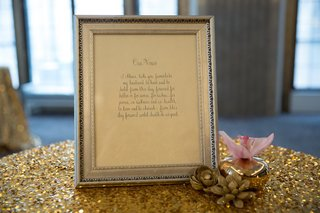 handwritten-vows-framed-in-silver-frame-on-gold-sequin-tablecloth